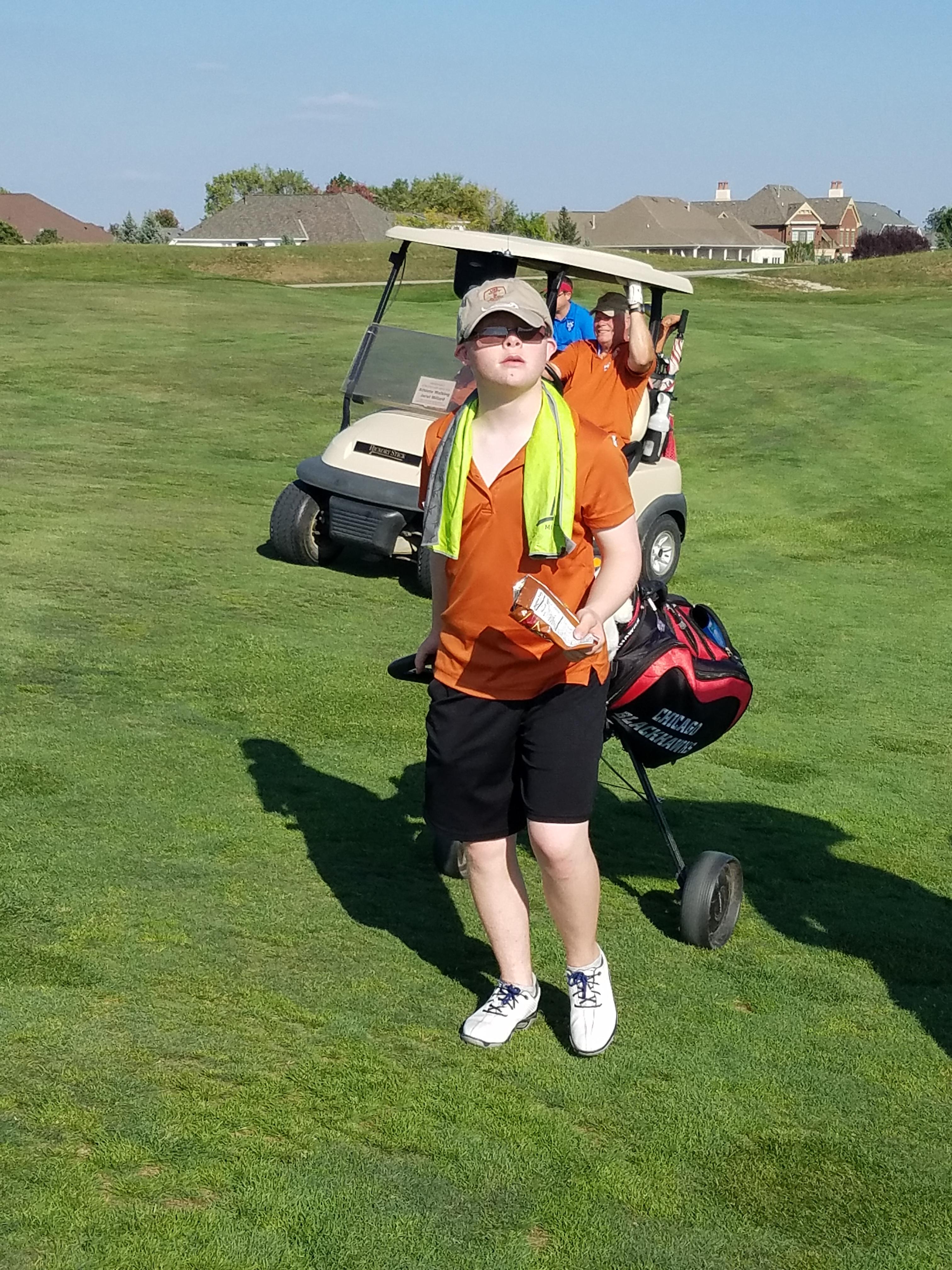 Zack Millard in front of his golf cart
